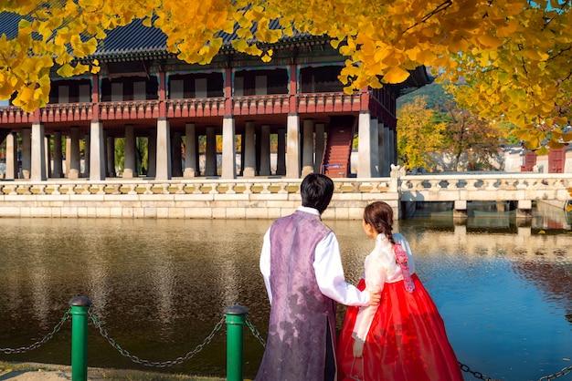 韓服の男女がイチョウの秋の庭でソウル宮殿を歩く
