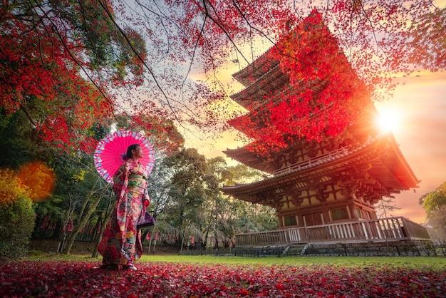 着物の伝統的な衣装で日本人の女の子が公園を散歩します。