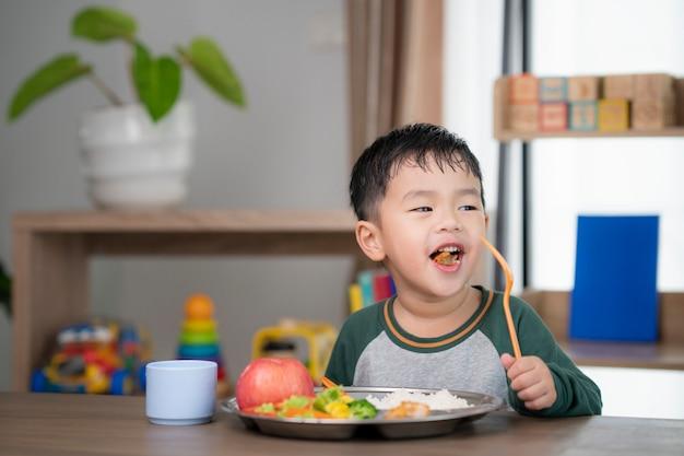 アジアの学生は彼の幼稚園によって準備された食品トレイによってクラスルームでランチを取る、この画像は、食品、学校、子供、教育の概念に使用できます。