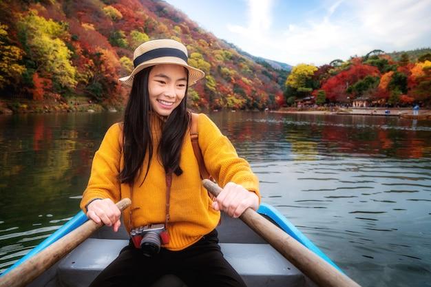 アジアの女の子は嵐山公園の川でパドルとレンタルボートでリラックスします。