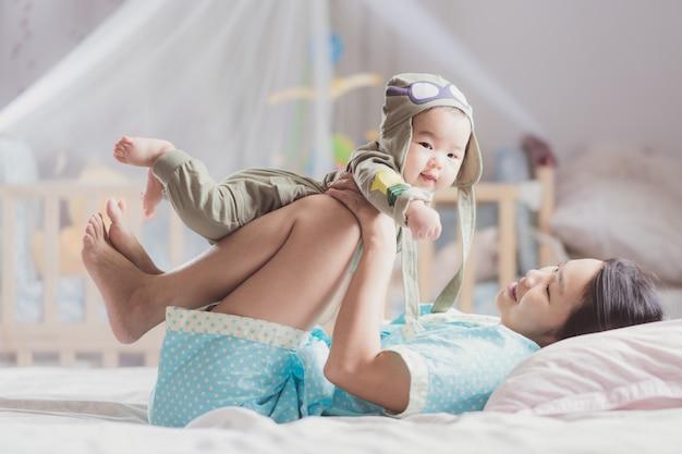 ベッドで彼女の赤ちゃんと遊ぶ母