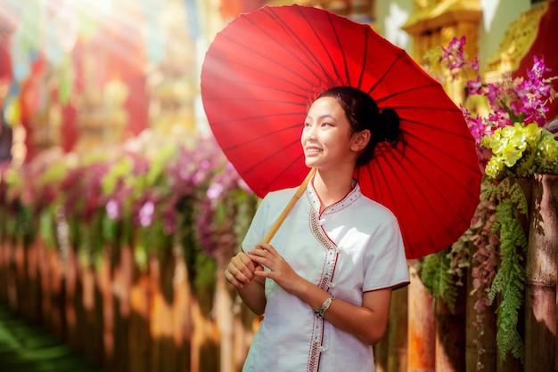Азиатская девушка в северном традиционном костюме и красный зонт