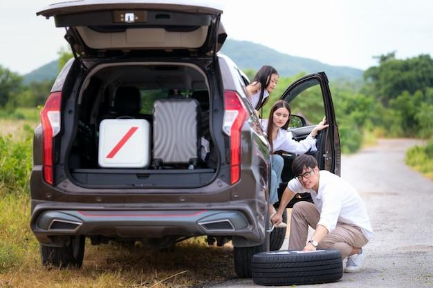 父はタイヤを交換し、彼の家族は旅行の間に待っています