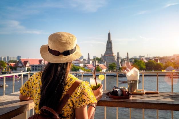 Азиатская девушка сидит и отдохнуть в ват с фоном храма ват арун
