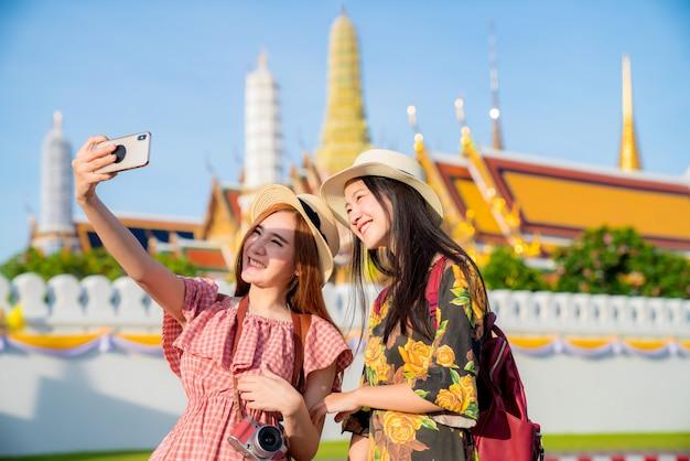 Две азиатские подружки путешествуют и фотографируются в гранд палас и ват пхра кео