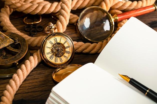 Античные часы на предпосылке винтажной тетради и ручки. чистый лист для написания текста.