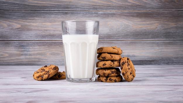 Стопка шоколадного печенья лежит возле стакана молока. кальций богатое молоко.