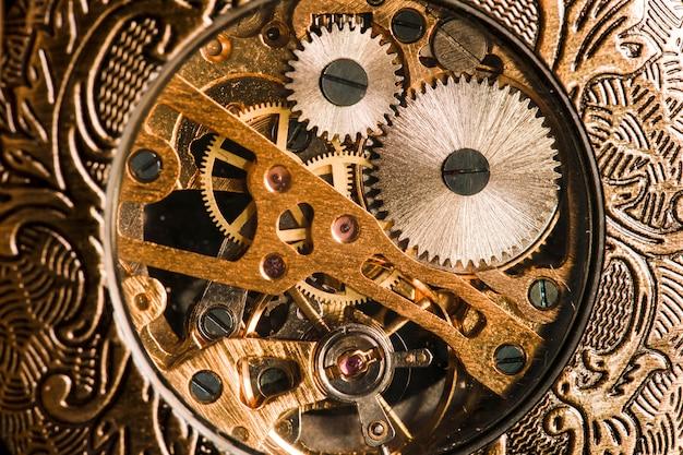 Старинные часы на фоне старинных книг. механический часовой механизм на цепочке.