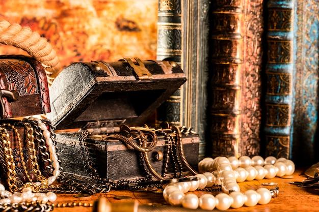 Сундуки с сокровищами с золотом. жемчуг и золотые цепочки. винтажный стиль.