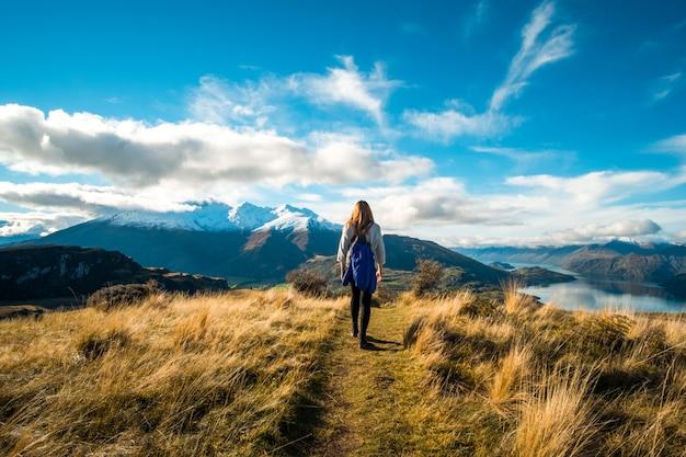 高山の黄色い草でハイキングする女性。青い空、湖、山と夕日の光。
