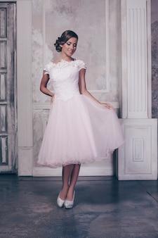 カジュアルな白いドレスと腰に腕を保持している黒のハイヒールでポーズをとって長いウェーブのかかった髪の豪華なスリムな女性の全身ショット