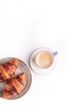 クロワッサンと白い木製のテーブルの上のコーヒーカップ。朝の静物。テキスト用のスペースを持つトップビュー。フラットレイアウト構成。レストラン、パン屋、カフェの背景。