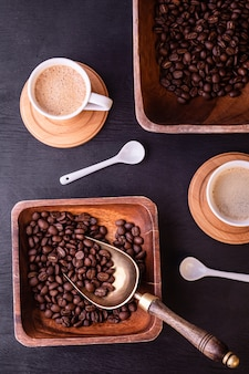 コーヒーのテーマ。熱い一杯のコーヒーと黒い木製テーブルの上のコーヒー豆とプレート。