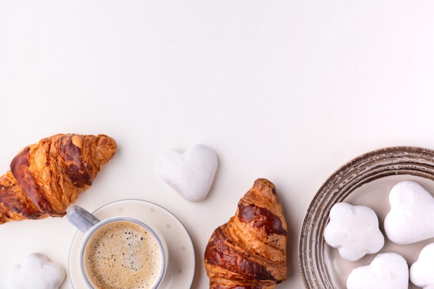 クロワッサン、艶をかけられたクッキー、白い木製のテーブルの上のコーヒーカップ