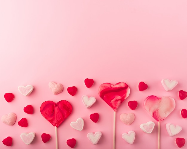 Розовый романтический праздник фон с в форме сердца, сладкие конфеты. декоративная открытка на день святого валентина с пространством для текста. любовная тема.