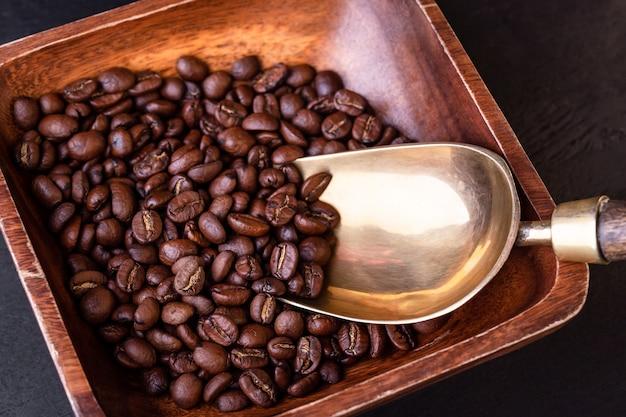コーヒーのテーマ。黒い木製のテーブルにコーヒー豆とプレート。ビンテージ銅スクープ。