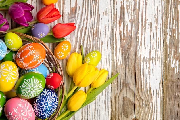 Пасхальные яйца и тюльпаны на деревянных нарах