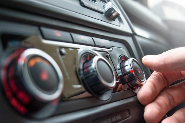 車の座席のクローズアップを加熱するためのボタン。男性の手が車の座席を加熱するためのボタンを押します。