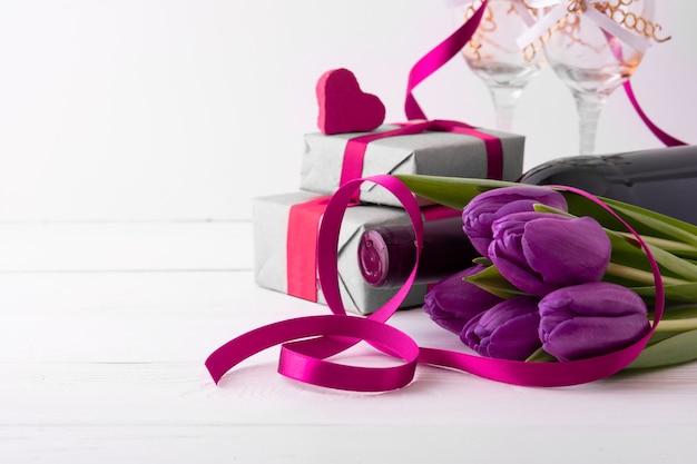 女性の日。花と白い壁のワインのギフト