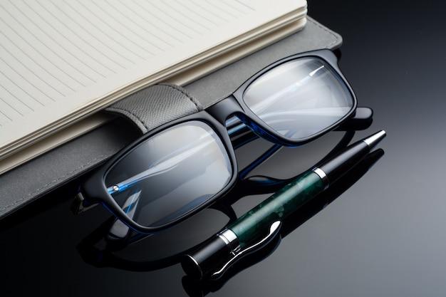 メガネ、ペン、黒いテーブルの上のノート