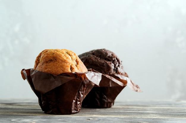 灰色の木製の背景にチョコレートとプレーンのカップケーキ。