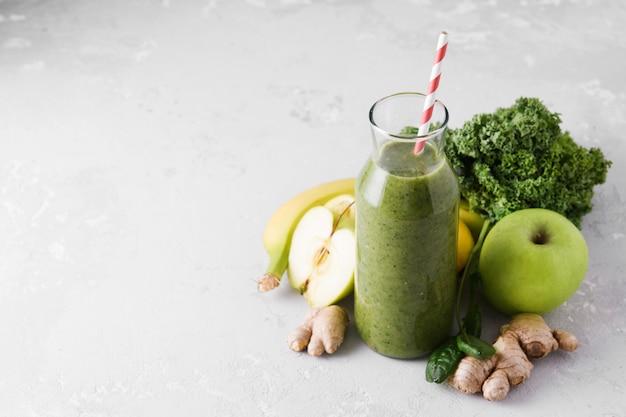Свежеприготовленные бутылки зеленого смузи, крупным планом.