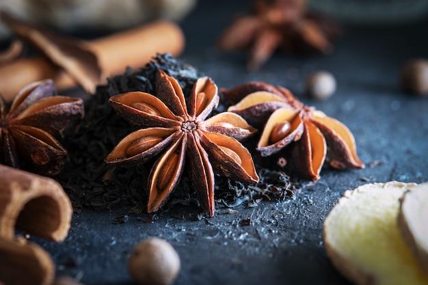 Анис звезды со специями и черный чай на синем фоне. рецепт приготовления чая масала.