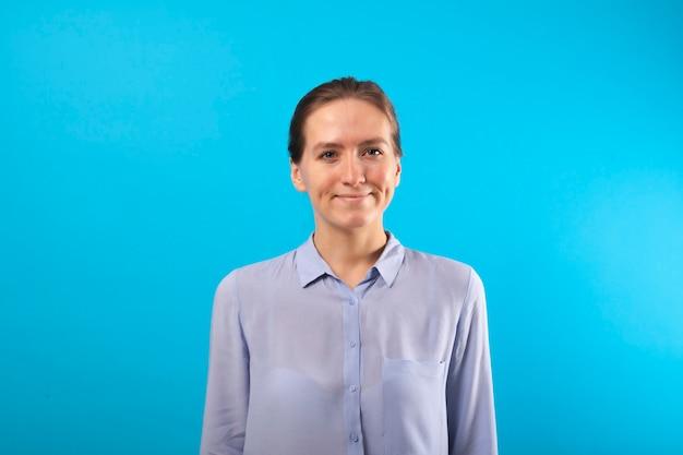 Улыбающиеся деловая женщина, одетая в синюю бизнес рубашку позирует на синем фоне. молодая девушка улыбается с ямочками на щеках.