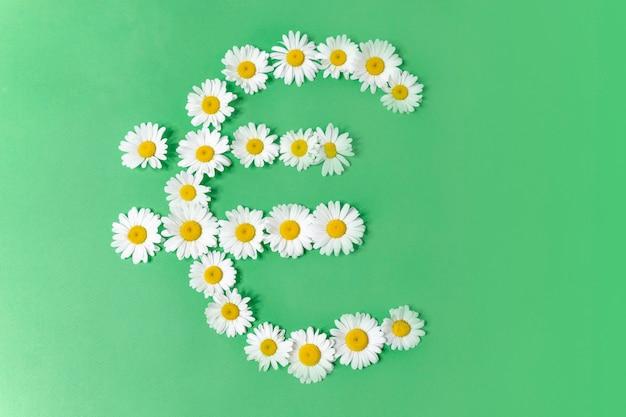 緑の背景にヒナギクの花で作られたお金のユーロ記号。