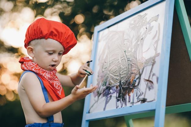 笑顔画家男のクローズアップ。自然に油絵を描く芸術家の少年の手