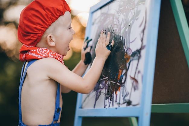 恥ずかしさに笑みを浮かべて、彼女の手で塗料を喜ぶ小さな男の子のクローズアップの肖像画