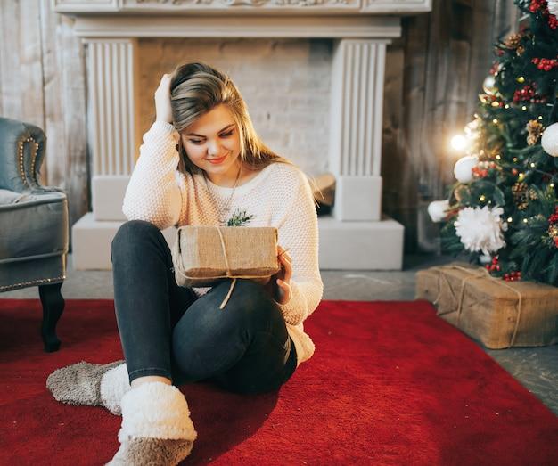 Женщина распаковывает рождественский подарок в комнате