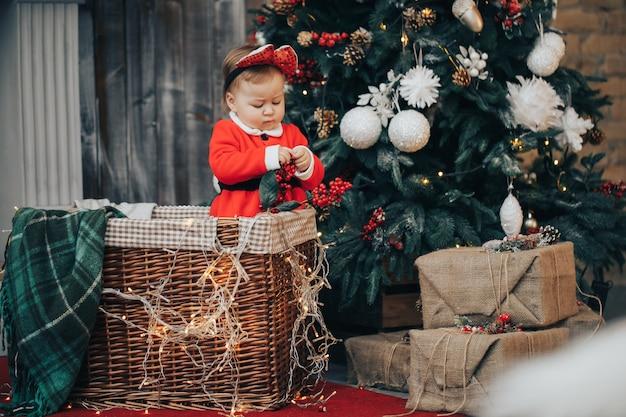 バックグラウンドでライトをサンタクロースの帽子とスーツを着てクリスマスボールで床の上でクロール赤ちゃんの女性