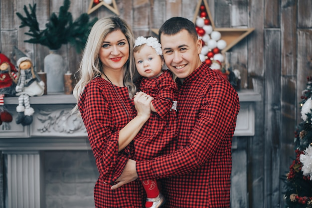 Счастливая семья со своей маленькой дочерью вместе в украшенной комнате