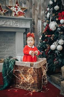 クリスマスライトが付いているバスケットのスーツの女の子