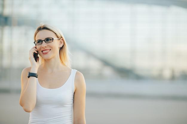 Стильная дама в очках разговаривает по телефону и улыбается