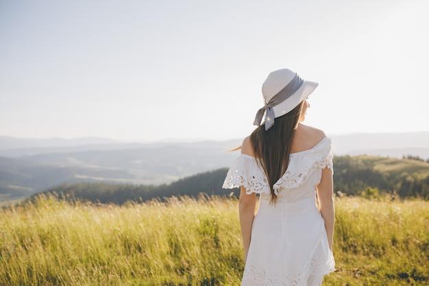 山の谷で走っている少女の背面図。喜びの幸せに興奮してフィールド自然で走って楽しんで幸せな女。