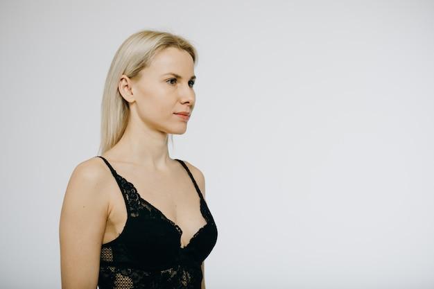 白で隔離される黒のランジェリーで金髪のモデル