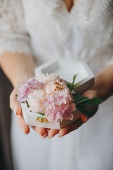 男性と女性のためのジュエリー。リングとカラフルな花束を保持している花嫁。結婚式のアクセサリー。