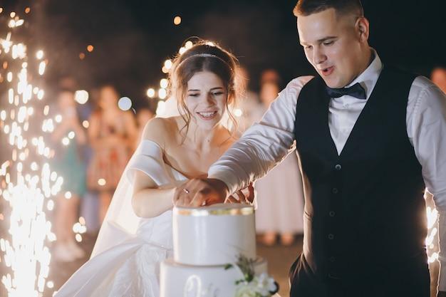 Красивая молодая пара свадьбы есть торт, гости с бенгальскими огнями. жених и невеста разрезали свадебный торт. счастливые молодые новобрачные пара резки свадебный торт в парке.