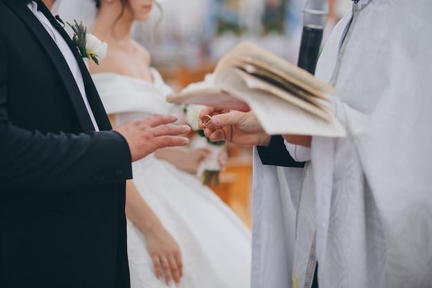 Священник надевает кольцо на палец жениха во время свадебной церемонии