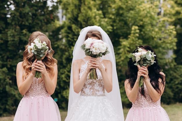 花嫁と二人の花嫁介添人のウェディングブーケ