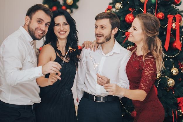 Счастливые парни и девушки наслаждаются новогодней вечеринкой с бенгальскими огнями