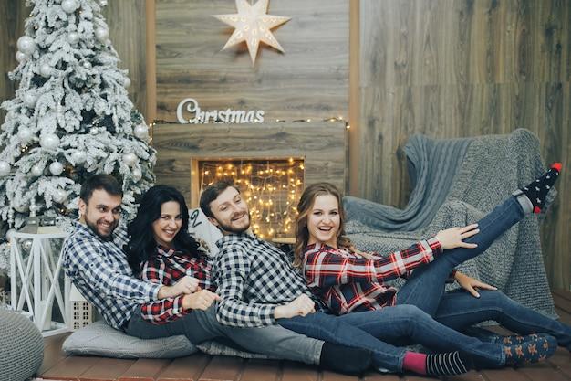 Портрет счастливых парней и девушек, наслаждающихся новогодней вечеринкой с рождественскими огнями