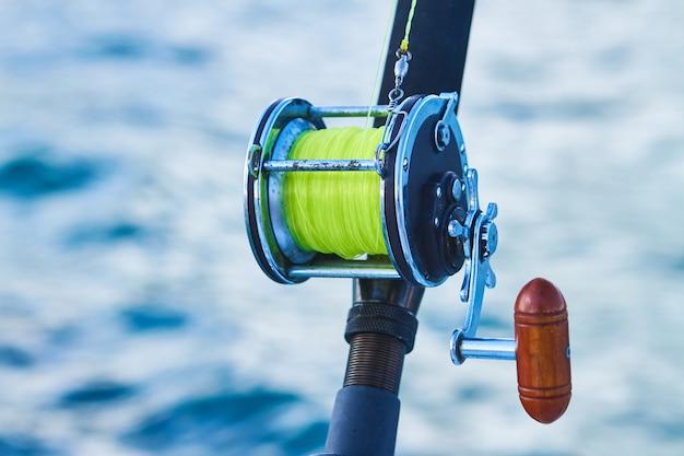 トローリングフィッシングボートロッドと金色の海水リールディープブルーの海海の航跡。ドミニカ共和国のプンタカナ漁船。