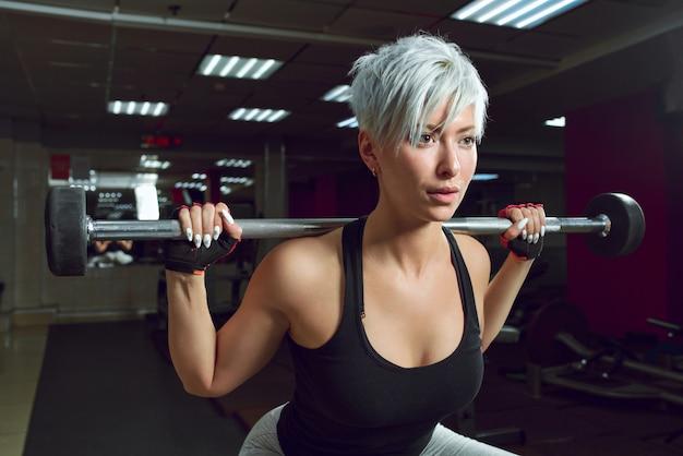 フィットネスルームでバーベルで筋肉をポンプ運動の女性