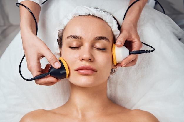 クリニックで化粧品の顔の治療を受ける女性