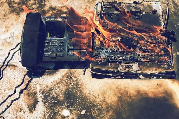 オフィス、火傷した電話とラップトップでの火災