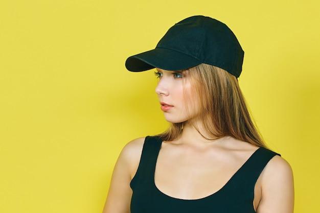 キャップでセクシーな若いヒップホップの女性。黄色の壁に