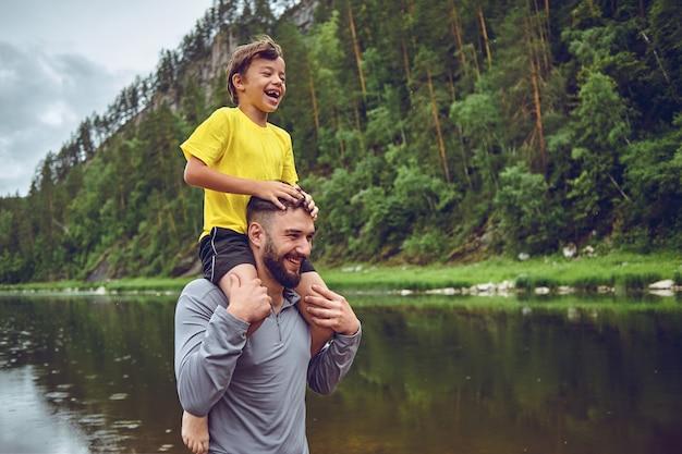 Веселиться. отец пример благородного человека. ребенок катается на плечах папы. счастье быть отцом мальчика.